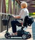 Mujer mayor conduciendo en un puente el Scooter Eclipse Plus compacto, desmontable y con baterías extraíbles