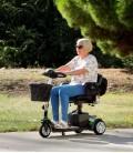 Mujer mayor conduciendo por la calle el Scooter Eclipse Plus compacto, desmontable, con baterías extraíbles y con accesorios