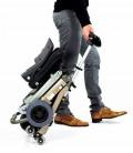 Scooter Luggie de aluminio, ligero, plegable y regulable en altura - persona transportando el scooter