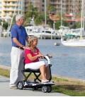 Mujer mayor maneja el scooter Quest Plegable acompañada con un hombre y miran paisaje