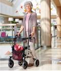 Señora de edad avanzada de pie en centro comercial utilizando el Andador ROLATOR LIGERO TAiMA