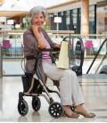 Señora de edad avanzada en centro comercial sentada en el asiento de tela del Andador ROLATOR LIGERO TAiMA