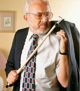Anciano utilizando el bastón con gancho para ayudar a vestirse a las personas mayores o con discapacidad