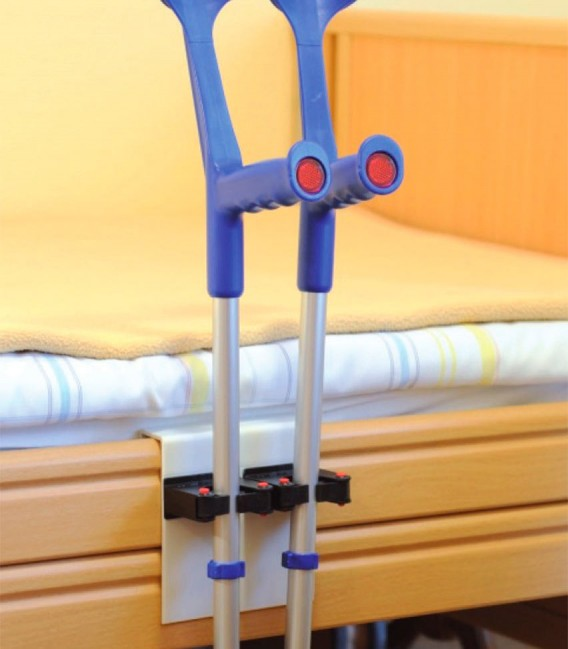 Soporte doble para bastones y muletas ejemplo de uso en una cama con dos muletas