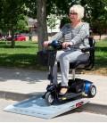 Señora bajando con Scooter Go Go de 3 ruedas azul por una rampa portátil en un parque