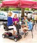 Señora haciendo uso del Scooter Go Go LX rojo en una terraza de una cafetería