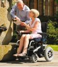 Pareja senior turista, la mujer hace uso de la silla de ruedas eléctrica robusta de tracción trasera mientras mira un mapa