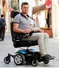 Joven haciendo uso en la ciudad de Silla de ruedas eléctrica compacta