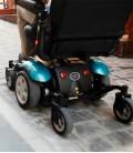 Detalle del kit azul y ruedas traseras de la silla de ruedas eléctrica compacta en una calle