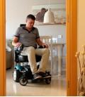 Joven haciendo uso en su casa de Silla de ruedas eléctrica compacta