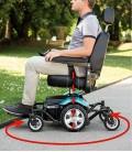 Joven en un parque hace un giro con la silla de ruedas eléctrica versátil