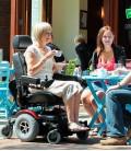 Señora de edad avanzada haciendo uso de la Silla de ruedas eléctrica robusta mientras toma un café en una t