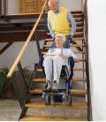 Pareja de edad avanzada haciendo uso de la silla sube escaleras Escalino en las escaleras de su casa