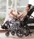 Señor de edad avanzada, haciendo uso de la silla de ruedas basculante Vip mientras lee el periódico en casa