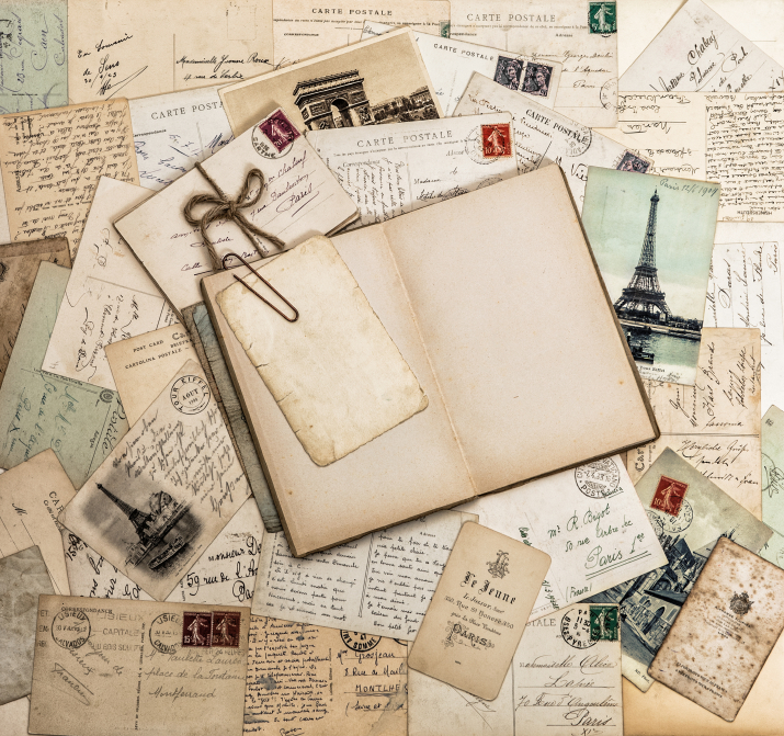Open book, old letters and postcards. Vintage style paper background. Travel scrapbook for France and Paris